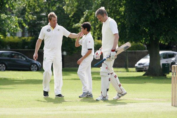 The great man: Shane Warne, left, shares a word with a young cricketer and Richmond Park MP Zac Goldsmith last week