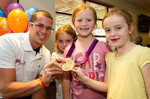 Surgery required: Hampton's James Foad shows off his medal to children at his David Lloyd Hampton