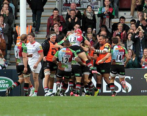 Celebrate: Quins players mob Danny Care after his first half score gave Quins 13-9 advantage at the break