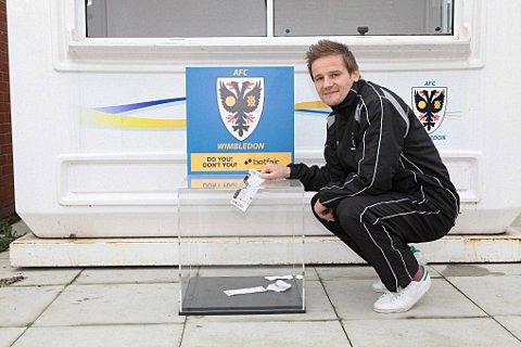 Ticket amnesty: Dons boss Neal Ardley drops his ticket in the box, but of course he does not need one anyway