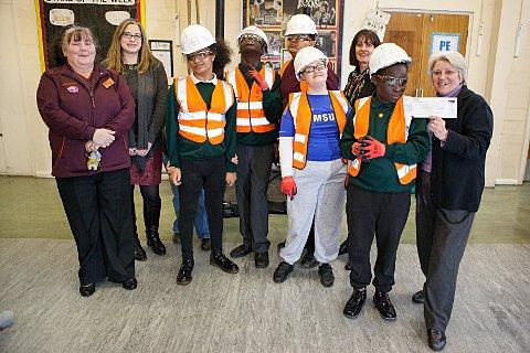 Children from Priory School try on the high vis jackets