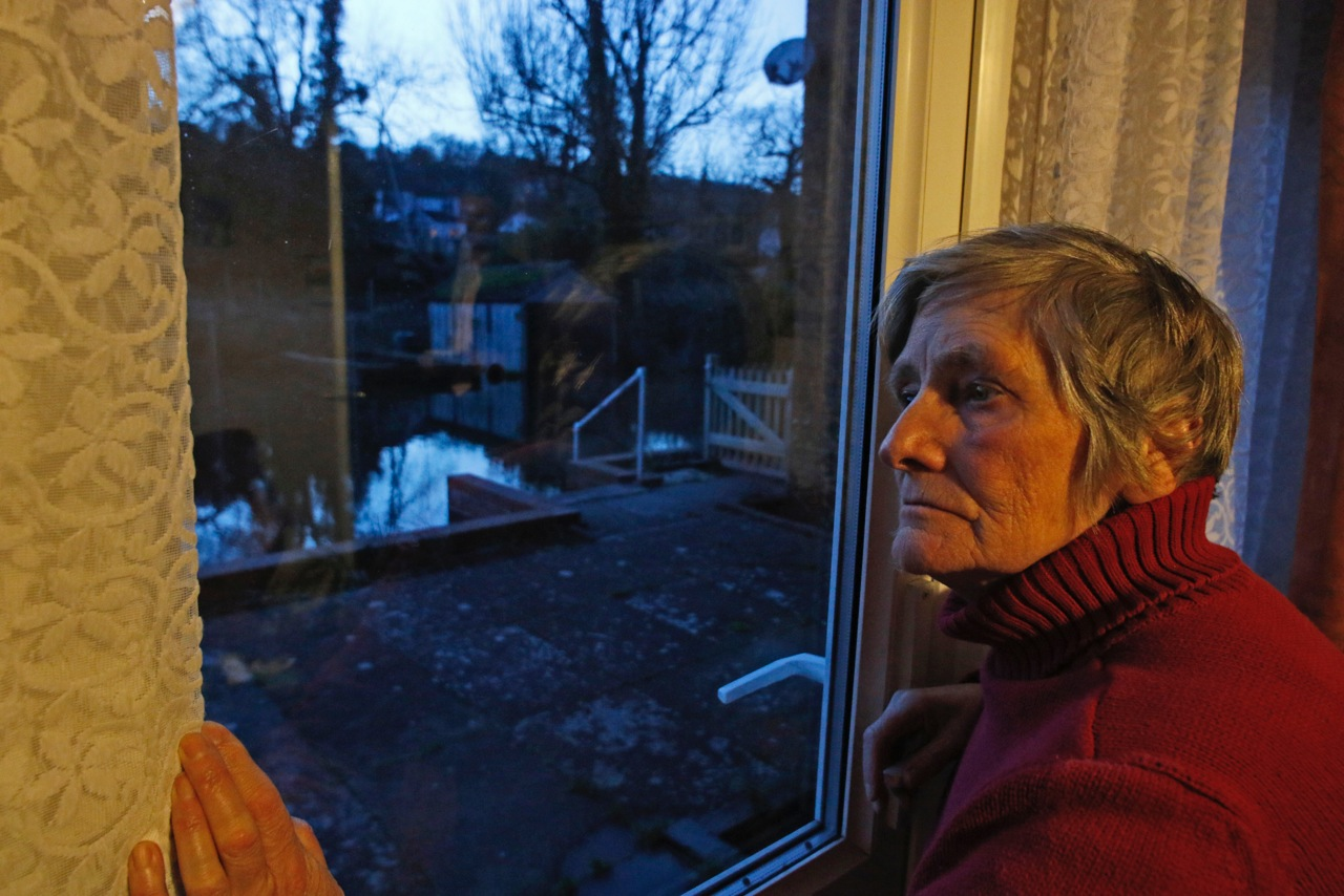 Thelma Choppin looks at her flooded garden hoping water will come no closer to her home