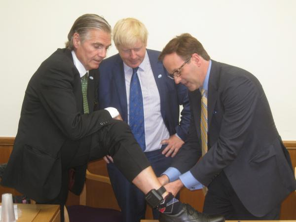 Mayor of London Boris Johnson watches as London Assembly member for Croydon and Sutton Steve O'Connell has his sobriety tag removed