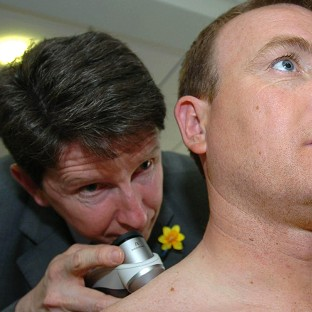 A dermatologist checks skin for signs of cancer