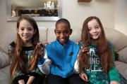 Malachi Reid holds Sienna and Scarlett Hewitt's hair at the level where it will be cut off